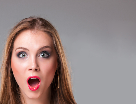 woman mouth open: Close-up portrait of surprised beautiful gir over gray background. Copyspace image