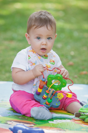teething: Baby, less than a year old playing with a toy on a background of green grass Stock Photo