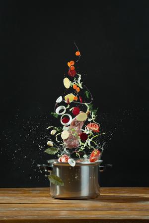 steel pan: Las verduras frescas caer en una cazuela de acero inoxidable en la mesa de madera. El concepto de borsch cocinar Foto de archivo