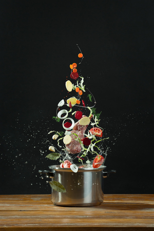 Fresh vegetables falling into a stainless steel casserole on wooden table. The concept of cooking borsch