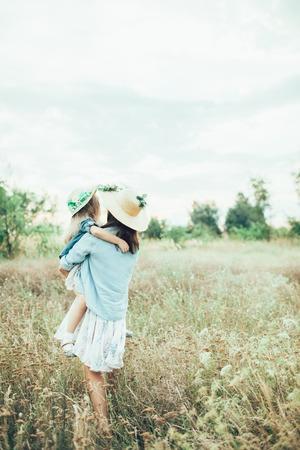 Die Rückansicht der jungen Mutter und Tochter mit Hüten auf grünem Gras Hintergrund