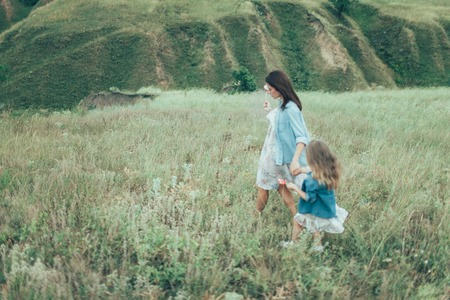 mum and daughter: The young mother and daughter  on green grass background