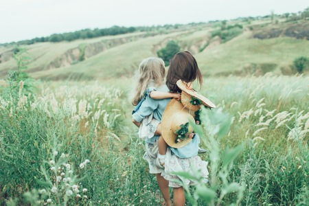The back view of young mother and daughter on green grass background. Stock Photo