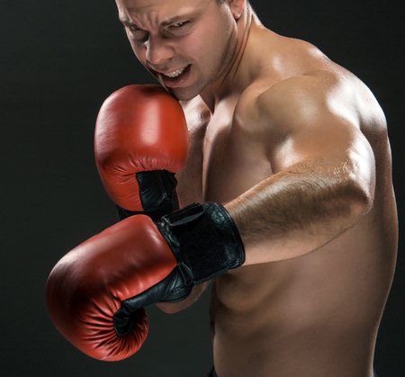 punched out: Young boxer in red gloves boxing over black background Stock Photo
