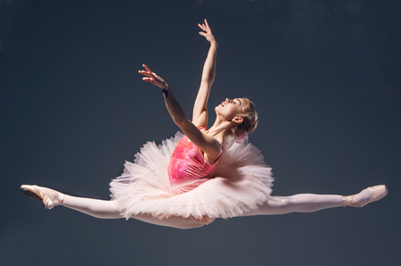 ballet: Beautiful female ballet dancer jumping on a gray background. Ballerina is wearing in  pink tutu and pointe shoes