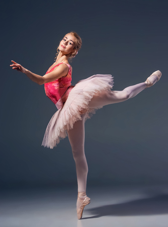 Beautiful female ballet dancer  on a gray background. Ballerina is wearing in  pink tutu and pointe shoes Фото со стока