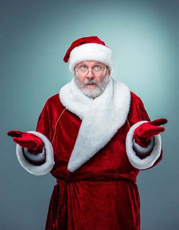 Wondering Santa Claus looking at the camera  in glasses with a gray beard and raised arms on a blue background