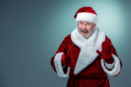 gray beard: A happy, smiling Santa Claus in glasses with a gray beard on a blue background