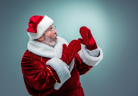 wondering: Wondering Santa Claus in profile with a gray beard on a blue background