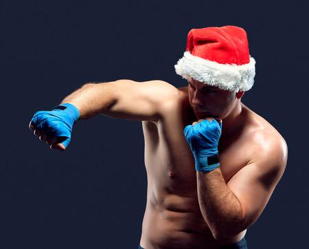 male body: Christmas fitness boxer wearing santa hat boxing on black background Stock Photo