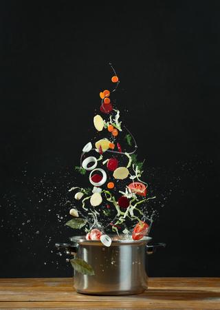 mosca: verduras frescas caer en una cacerola de acero inoxidable sobre la mesa de madera. El concepto de cocinar comida vegetariana