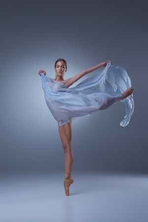 De mooie ballerina dansen met blauwe sluier op een blauwe achtergrond