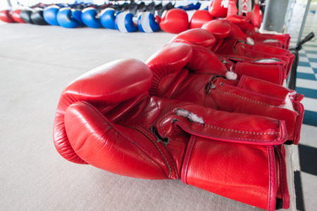 thai boxing: The pairs of red and blue  boxing gloves on gray background