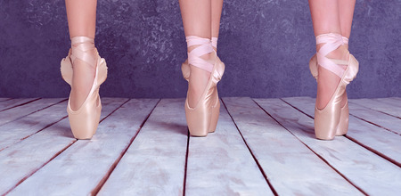 ballerina: The close-up feet of a three young ballerinas in pointe shoes against the background of the wooden floor