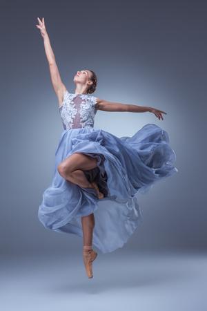 The beautiful ballerina dancing in long blue dress on blue background Foto de archivo