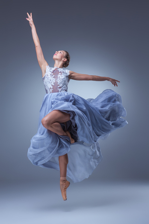 The beautiful ballerina dancing in long blue dress on blue background 스톡 콘텐츠