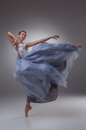 pointes: The beautiful ballerina dancing in long blue dress on blue background Stock Photo
