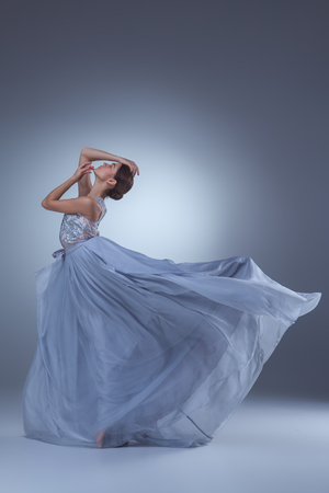 The beautiful ballerina dancing in long lilac dress on lilac background