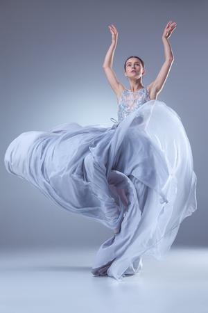 라일락 배경에 긴 라일락 드레스에 춤을 아름 다운 발레리 나는 스톡 콘텐츠