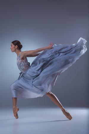 Die schöne Ballerina tanzen in langen lila Kleid auf lila Hintergrund Standard-Bild