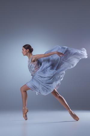 danza contemporanea: La hermosa bailarina bailando en vestido lila largo en fondo de la lila