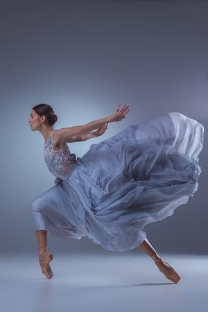 danza clasica: La hermosa bailarina bailando en vestido lila largo en fondo de la lila
