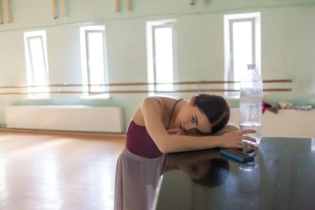 weary: The weary classic ballet dancer in a  rehearsal room background