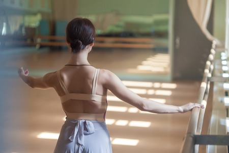 barre: The classic ballet dancer posing at ballet barre on a  rehearsal room background. back view Stock Photo