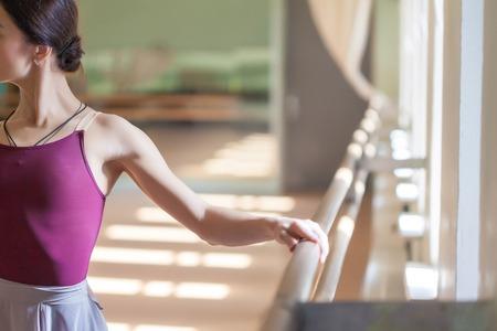De klassieke balletdanser stellen bij ballet barre op een oefenruimte achtergrond Stockfoto