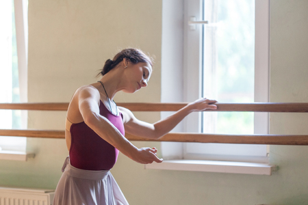 barre: The classic ballet dancer posing at ballet barre on a  rehearsal room background Stock Photo