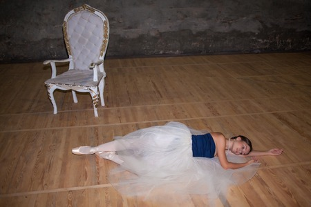 pointes: The beautiful ballerina lying in long white skirt on wooden floor background