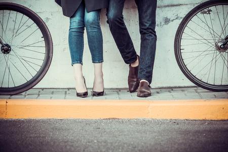 piernas con tacones: Las piernas de pareja de j�venes sentados en las bicicletas frente a la ciudad Foto de archivo