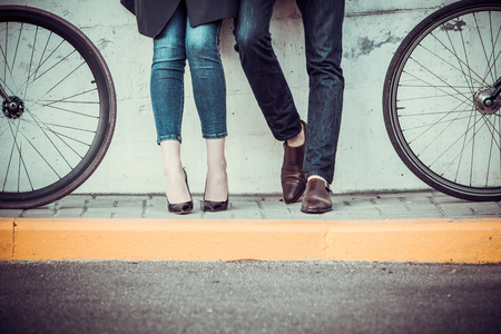man legs: The legs of young couple sitting on bicycles opposite the city