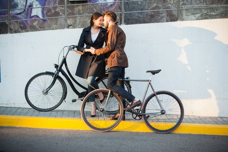 and opposite: Young couple with a bicycle opposite the city