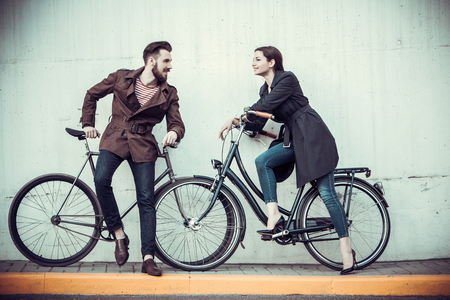 urban life: Young couple with a bicycle opposite the city