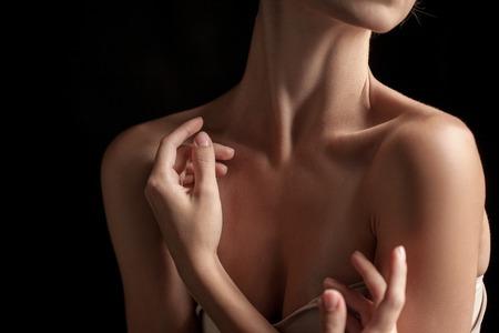 jeune femme nue: Le gros plan du cou et les mains d'une jeune femme sur fond sombre