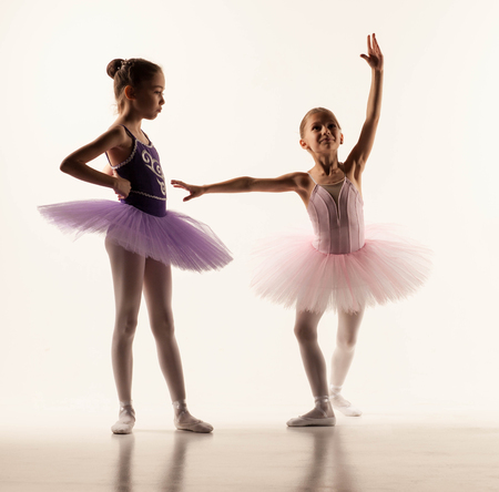 young: The two little ballet girls in tutu standing against white studio