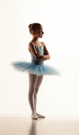 bebes niñas: niña de ballet en tutú de pie contra el estudio de blanco
