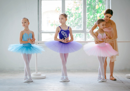 kids class: Three little ballerinas with personal ballet teacher in dance studio on a white background