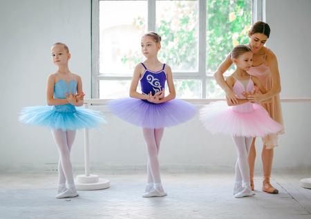 Tres pequeñas bailarinas de ballet con el maestro personal en el estudio de danza sobre un fondo blanco