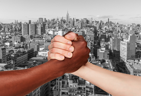 show of hands: Black and white human hands in business handshake to show each other friendship and respect against  Manhattan skyscrapers Stock Photo