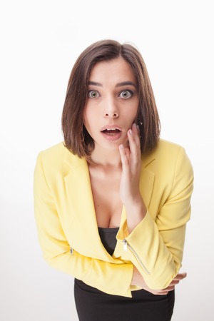 yellow jacket: The picture of surprised beautiful business woman in a yellow jacket on white background