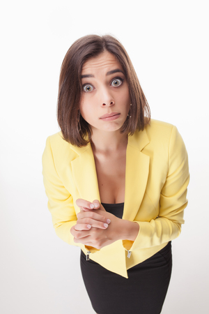 wonderment: The picture of surprised beautiful business woman in a yellow jacket on white background
