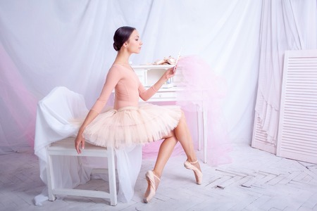 pointes: Professional ballerina looks in the mirror against the backdrop of pink veil and  pointes Stock Photo