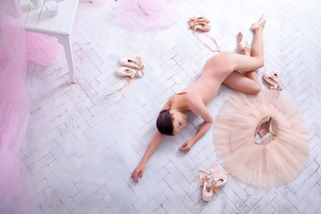 pointes: Professional ballerina resting after the performance against the backdrop of pink veil and  pointes Stock Photo