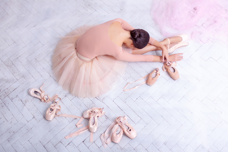 ballerina girl: Professional ballerina resting after the performance against the backdrop of pink veil and  pointes Stock Photo