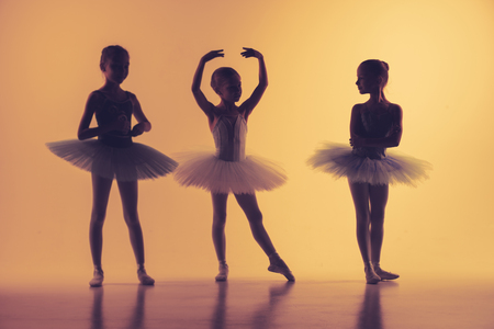 The silhouettes of little ballerinas in dance studio posing on a orange background