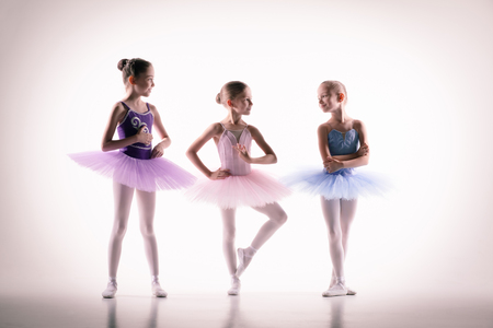 DAnce background: The silhouettes of little ballerinas in dance studio posing on a white background