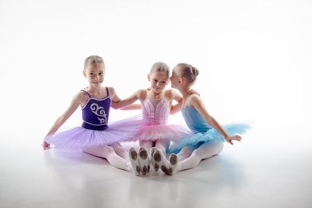 lindo: Tres ni�as de ballet que se sientan en los zapatos del pointe tutus y multicolores juntos sobre fondo blanco