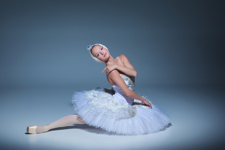 swan lake: Portrait of the ballerina  in the role of a white swan on blue background Stock Photo